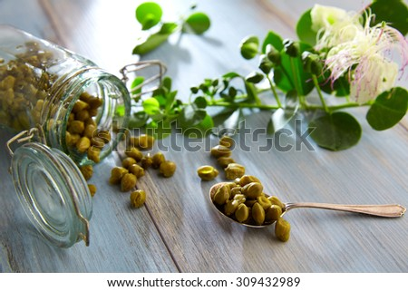 Capers pickled with plant and caper plant flower on vintage spoon