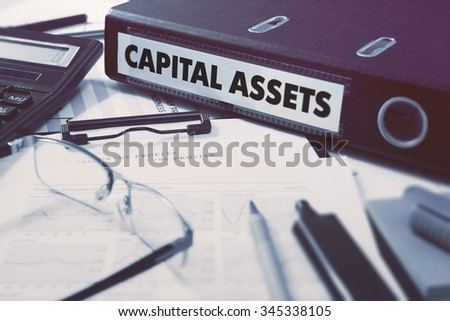 Capital Assets - Office Folder on Background of Working Table with Stationery, Glasses, Reports. Business Concept on Blurred Background. Toned Image. - stock photo
