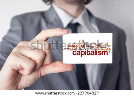 Capitalism. Businessman in suit with a black tie showing or holding business card - stock photo
