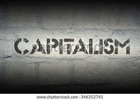 capitalism word stencil print on the grunge white brick wall