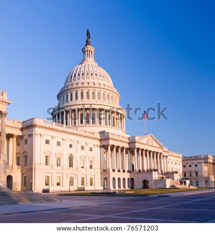 Capitol building in Washington DC illuminated early in the morning by the rising sun and giving a red/orange hue to the traditional scene - stock photo