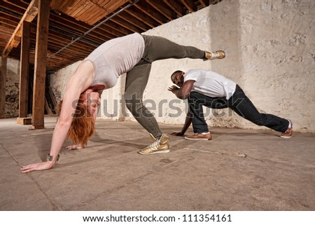 Capoeria artist performs spinning back kick on partner - stock photo