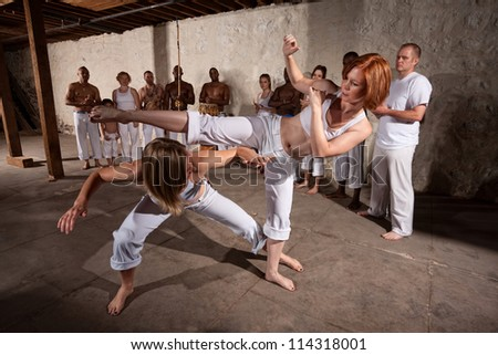 Capoeria martial artists performing techniques on concrete floor - stock photo