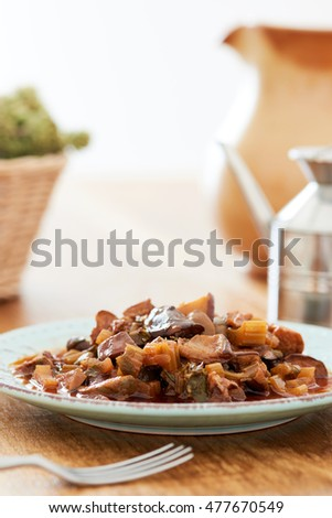 Caponata on a blue plate on a country wooden table, surrounded by rosemary, oil, and a water glass