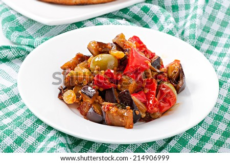 caponata with raisins and pine nuts decorated with a leaf of basil - stock photo