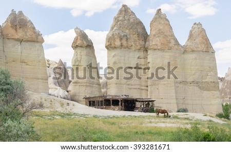 Cappadocia Goreme. Cappadocia Rural view . Cappadocia landscape. Stone houses of Cappadocia. Sunny Goreme Cappadocia. Countryside lifestyle of Cappadocia. Horse pasture in Cappadocia. Mountains peaks - stock photo