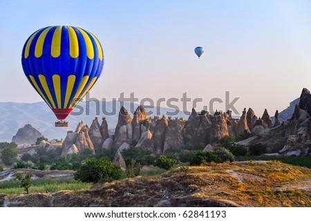 Cappadocia hot air balloon flying over bizarre rock landscape in Turkey - stock photo