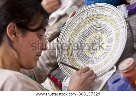CAPPADOCIA, TURKEY APRIL 17: Artist adds detail to a ceramic bowl with animal design patternon April 17, 2012 in Cappadocia, Turkey. - stock photo