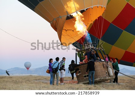 Cappadocia, Turkey -  August, 10 2013 :  Passengers climbing into hot air balloon basket. When the pilot is ready for launch, more heat is directed into the envelope and the balloon lifts off.  - stock photo