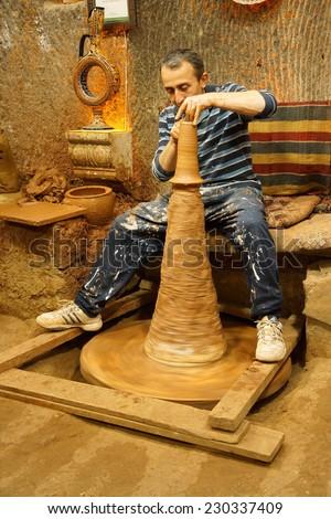 CAPPADOCIA, TURKEY - JUN 4, 2014 - Master craftsman makes pottery on a wheel, Avanos, Turkey - stock photo
