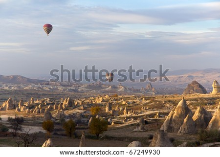 CAPPADOCIA, TURKEY - NOVEMBER 23: Tourists Enjoy the Unique Valleys and Fairy Chimneys While Floating Over Cappadocia at Sunset in Colorful Hot Air Ballons On November 23, 2010 in Cappadocia, Turkey - stock photo