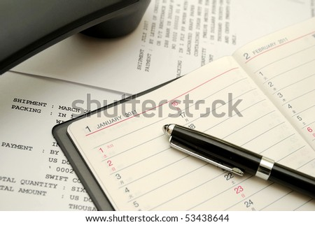 Capped black pen on planner with phone signifying concepts such as office and business, planning for the new year, financial budget and work related objects