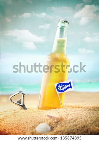 Capped bottle of chilled fruity orange soda or ale (beer) standing in the golden sand on a tropical beach with a bottle opener and Skipper sign. Look at my portfolio for more cocktails. - stock photo