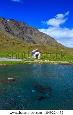 Cappella chapel on the lakeside at Foscagno Pass, Dolomites mountain range, Sondrio, Lombardy, Northern Italy.