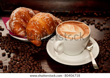 Cappuccino and croissant with coffee bean - stock photo