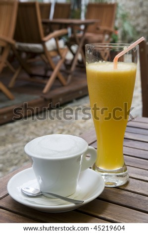 Cappuccino and orange juice on the table outdoor - stock photo