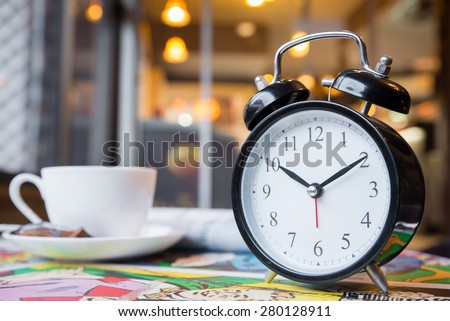 cappuccino and retro alarm clock with blur coffee shop background  - stock photo
