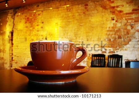 Cappuccino coffee cup and saucer in a funky interior - stock photo