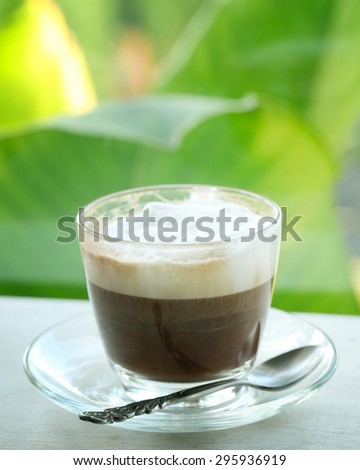 Cappuccino coffee cup on the table on nature backgrounds. - stock photo