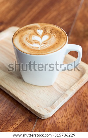 Cappuccino coffee cup on wooden dish - stock photo