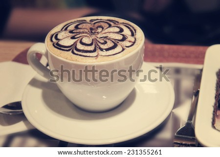 Cappuccino coffee cup with art foam. Retro vintage instagram filter - stock photo