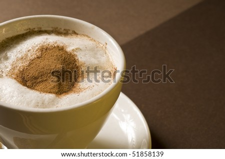 Cappuccino coffee drink over brown background