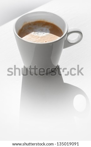 Cappuccino coffee in a ceramic cup on white table with shadow - stock photo