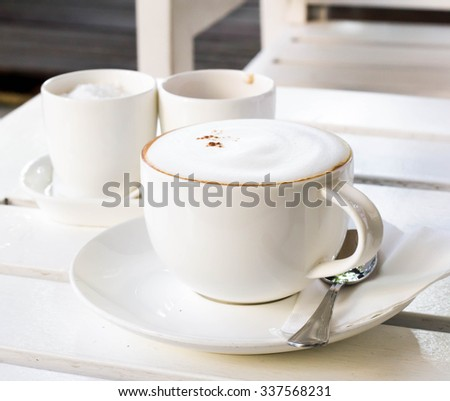 cappuccino coffee on white table - stock photo