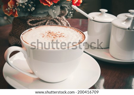 Cappuccino coffee with flower bouquet in vintage tone - stock photo