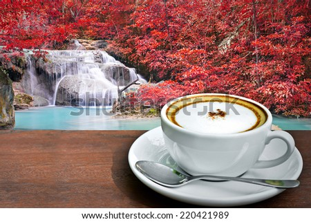 Cappuccino coffee with waterfall in autumn forest  - stock photo