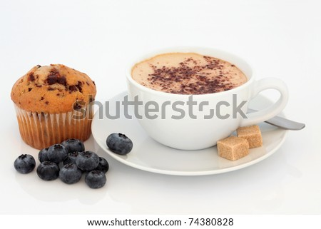Cappuccino cup and saucer with chocolate chip muffin and loose blueberry fruit, over white background. - stock photo