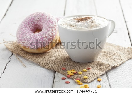 Cappuccino cup of coffee and donut  - stock photo