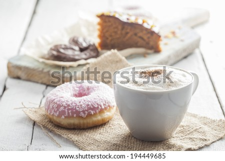 Cappuccino cup of coffee, donut and chocolate cake - stock photo