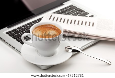 Cappuccino cup on laptop. Small DOF - stock photo