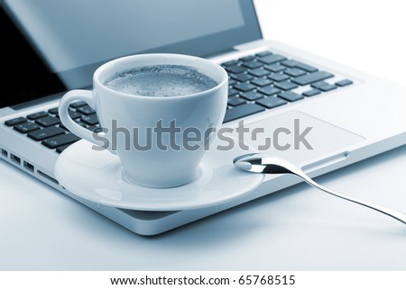 Cappuccino cup on laptop. Small DOF, blue toned