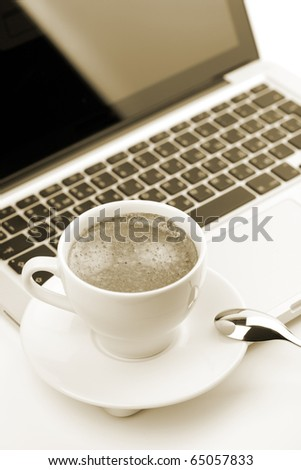 Cappuccino cup on laptop. Toned - stock photo