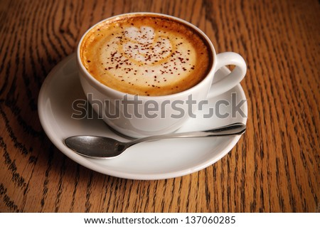 cappuccino cup on wooden table in cafe - stock photo