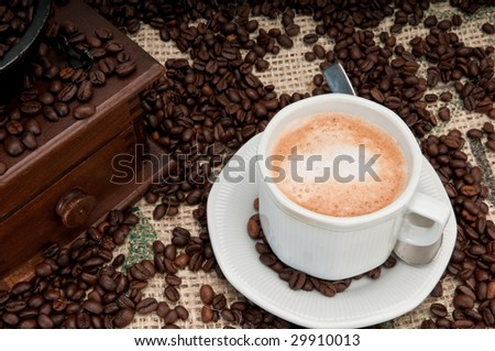 Cappuccino cup pf coffee wih old grinder and coffee beans. - stock photo
