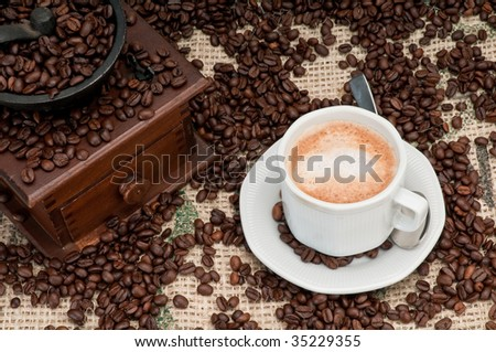 Cappuccino cup pf coffee with old grinder and coffee beans. - stock photo