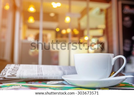 Cappuccino cup with blur coffee shop background, warm tone