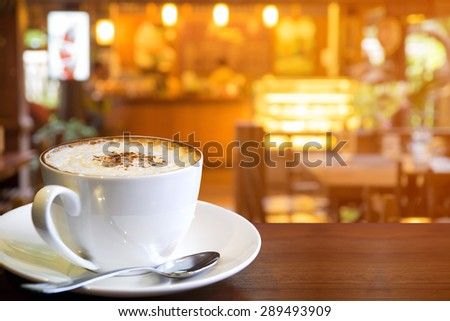 Cappuccino cup with blur coffee shop background, warm vintage tone  - stock photo