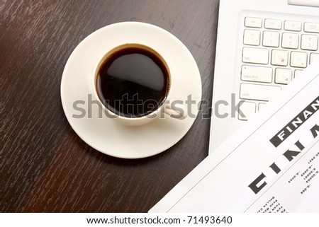 Cappuccino cup with laptop and newspaper. Blue toned - stock photo