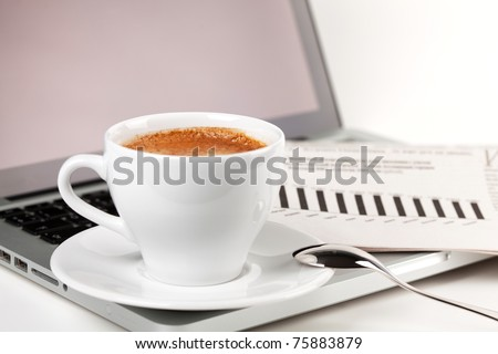 Cappuccino cup with laptop and newspaper. Small DOF - stock photo