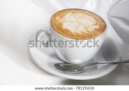 Cappuccino cup with spoon on white background - stock photo