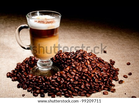Cappuccino glass with coffee beans on jute - stock photo