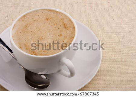 Cappuccino in a white ceramic cup with a saucer and a spoon. - stock photo