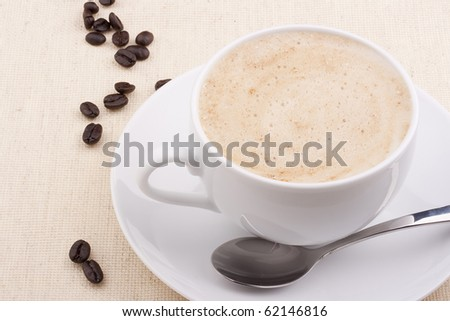 Cappuccino in a white ceramic cup with coffee grains. - stock photo