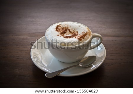Cappuccino in a white cup on a wooden table.