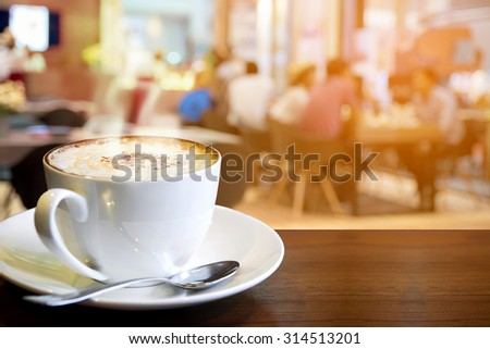 Cappuccino on the table with blur people in coffee shop background  - stock photo