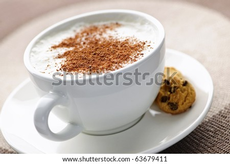 Cappuccino or latte coffee in cup with frothed milk and cookies - stock photo